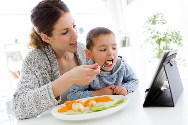 young-mother-her-son-using-digital-tablet-while-eating-fruits-home_1301-6192.jpg