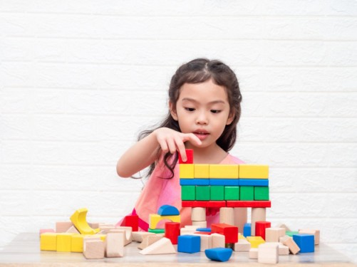 little-cute-girl-playing-wooden-blocks-table-white-bricks-wall-background_112781-103